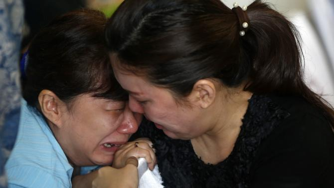 Family members of passengers onboard missing AirAsia flight QZ8501 cry at a waiting area in Juanda International Airport, Surabaya