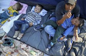 Migrants rest after crossing into the country from…