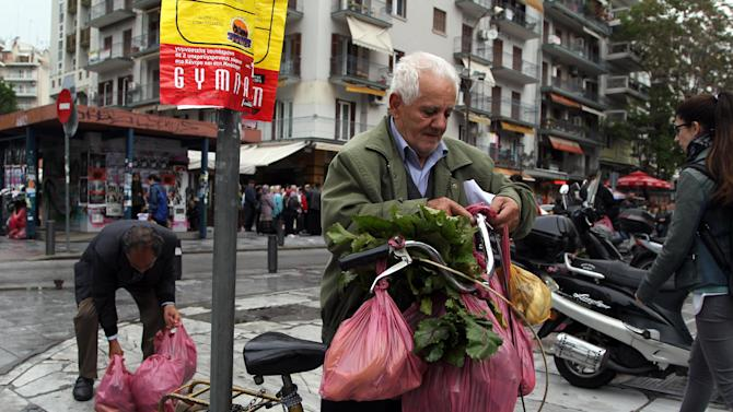 A man carries his produce after Greek farmers' market vendors distributed free produce as part of a protest in the northern Greek city of Thessaloniki, Wednesday, April 30, 2014, after their trading association launched an indefinite strike Monday. The market vendors are the latest professional group in Greece to protest a sweeping liberalization drive demanded by rescue creditors. (AP Photo/Nikolas Giakoumidis)