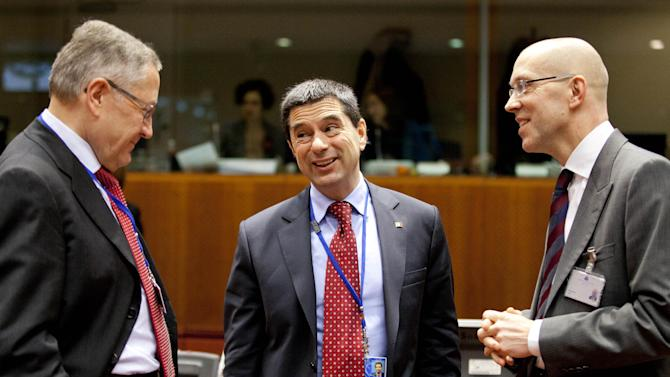 CEO of the European Financial Stability Facility, Klaus Regling, left, and member of the board of the ECB Joerg Asmussen, right, speak with Portugal's Finance Minister Vitor Gaspar during a meeting of EU finance ministers at the EU Council building in Brussels on Tuesday, Jan. 22, 2013. Eleven eurozone countries seeking to unilaterally implement a financial transaction tax are expected Tuesday to receive the blessing of other European Union countries, bringing the once-controversial project one step closer to reality. (AP Photo/Virginia Mayo)