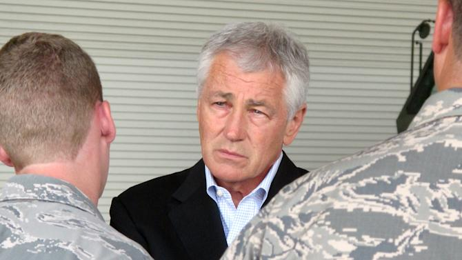 FILE - In this July 17, 2013, file photo. Defense Secretary Chuck Hagel talks with Air Force personnel at Joint Base Charleston near Charleston, S.C., on the last day of a three-day trip to visit bases in the Carolinas and Florida. A second, deeper round of automatic budget cuts is on its way, and it's going to hit the Pentagon hard. Already reeling from a $34 billion budget blow this year due to deficit-driven spending reductions known as sequestration, the Defense Department would feel an additional $20 billion pinch in 2014. All told, the Pentagon's budget for next year would be cut by about 10 percent below levels approved just six months ago. (AP Photo/Bruce Smith, File)