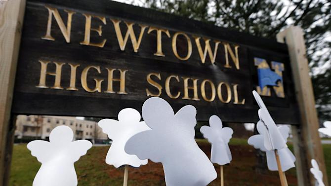 Angel cut-outs are displayed outside Newtown High School in Newtown, Conn., Sunday, Dec. 16, 2012. A gunman opened fire at Sandy Hook Elementary School in the town, killing 26 people, including 20 children before killing himself on Friday. (AP Photo/Charles Krupa)