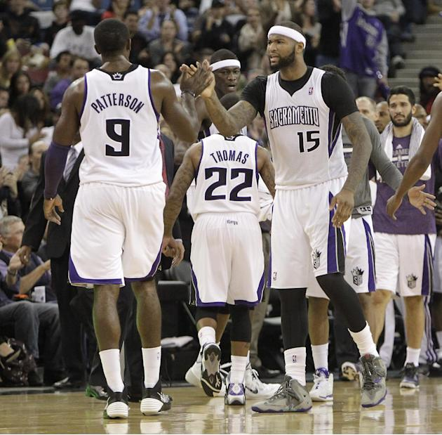 Sacramento Kings center DeMarcus Cousins, right, celebrates with teammate Patrick Patterson during a timeout in the closing moments of an NBA basketball game against the Phoenix Suns in Sacramento, Ca