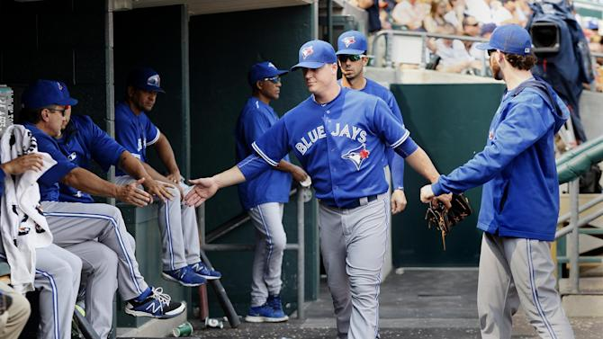 Toronto Blue Jays pitcher Aaron Loup, center, receives congratulations as he walks through the dugout after being pulled in the eighth inning of a baseball game against the Detroit Tigers Sunday, July 5, 2015, in Detroit. The Blue Jays defeated the Tigers 10-5. (AP Photo/Duane Burleson)