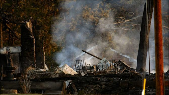 In this photo provided by Darrell Spangler, rubble smolders Sunday, June 24, 2012, from a home consumed by fire a day earlier, in Estes Park, Colo. As many as 21 structures were destroyed by the fire on Saturday. Eight separate wildfires are burning across Colorado, which is seeing record-breaking heat. (AP Photo/Darrell Spangler) MANDATORY CREDIT