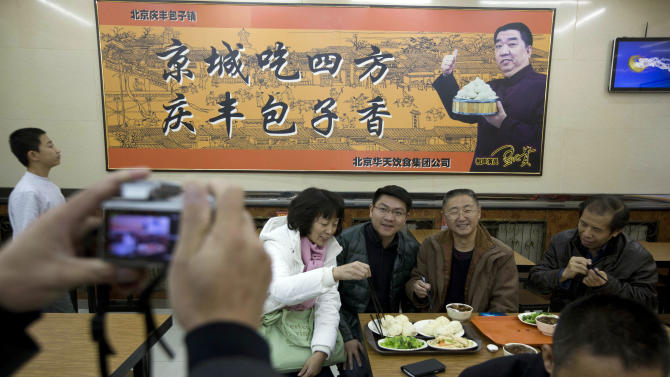 """Tourists from Guangdong province, who ordered similar food to what Chinese President Xi Jinping ate the day before, pose for photos at the Qing-Feng Steamed Dumpling Shop in Beijing, China, Sunday, Dec. 29, 2013. Xi dropped in unexpectedly Saturday at the traditional Beijing bun shop, where he queued up, ordered and paid for a simple lunch of buns stuffed with pork and onions, green vegetables, and stewed pig livers and intestines. The sign in the background is an advertisement for the restaurant which reads """"Capital city food from all places, Qing-Feng buns are fragrant."""" (AP Photo/Ng Han Guan)"""