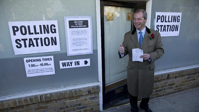 Nigel Farage the leader of the UK Independence Party (UKIP) poses for photographers as he arrives to cast his vote at a polling station in Ramsgate, south east England, Thursday, May 7, 2015. Polls have opened in Britain's national election, a contest that is expected to produce an ambiguous result, a period of frantic political horse-trading and a bout of national soul-searching.  (AP Photo/Matt Dunham)