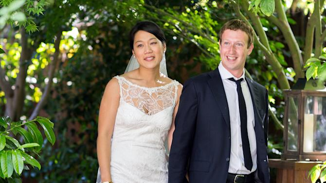 "This photo provided by Facebook shows Facebook founder and CEO Mark Zuckerberg and Priscilla Chan at their wedding ceremony in Palo Alto, Calif., Saturday, May 19, 2012. Zuckerberg updated his status to ""married"" on Saturday. The ceremony took place in Zuckerberg's backyard before fewer than 100 guests, who all thought they were there to celebrate Chan's graduation. (AP Photo/Facebook, Allyson Magda Photography)"