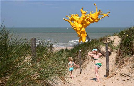 Girls run in front of a sculpture entitled Olnetop, magnified splashing waves, by Belgian artist Nick Ervinck, during the Beaufort04 Triennial of Contemporary Art exhibition along the Belgian coast, in Bredene, Wednesday, June 20, 2012. (AP Photo/Yves Logghe)