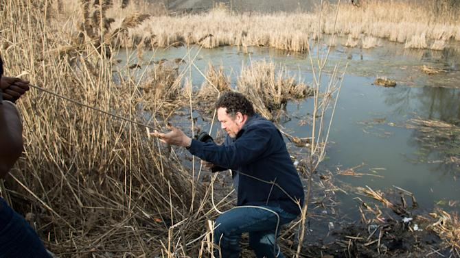 Beduareo Marquez climbs up the pond embankment where he retrieved a shoe from the crash site that six teens died on Park Ave. in Warren, Ohio on Sunday, March 10, 2013. (AP Photo/Scott R. Galvin)