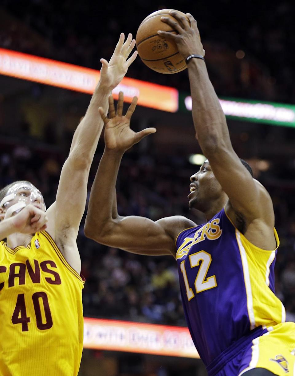 Los Angeles Lakers' Dwight Howard (12) shoots over Cleveland Cavaliers' Tyler Zeller in the third quarter of an NBA basketball game, Tuesday, Dec. 11, 2012, in Cleveland. Howard score 19 points and grabbed 20 rebounds, but the Cavaliers won 100-94. (AP Photo/Mark Duncan)