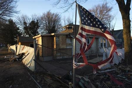 A torn U.S. flag flutters near a house destroyed by Superstorm Sandy at Staten Island in New York January 4, 2013. REUTERS/Eduardo Munoz