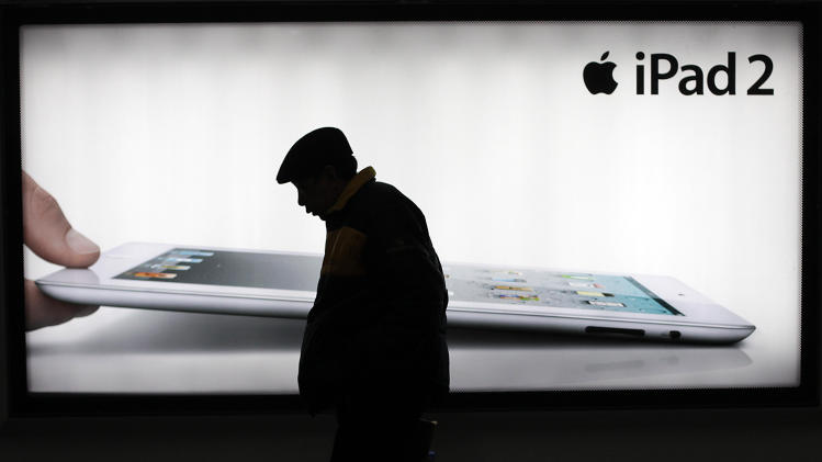 FILE - In this Tuesday, Feb. 28, 2012 file photo, a man walks past an advertisement of Apple's iPad 2 in Shanghai, China. Apple apologized to Chinese consumers after government media attacked its repair policies for two weeks in a campaign that reeked of economic nationalism. (AP Photo/Eugene Hoshiko, File)