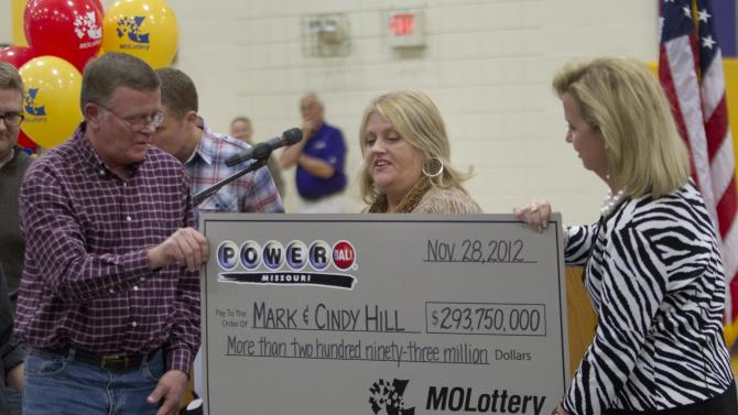Mark, left, and Cindy, center, Hill are presented a check by a Missouri Lottery official during the announcement of Powerball winners in Dearborn, Mo., Friday, Nov. 30, 2012. (AP Photo/Orlin Wagner)