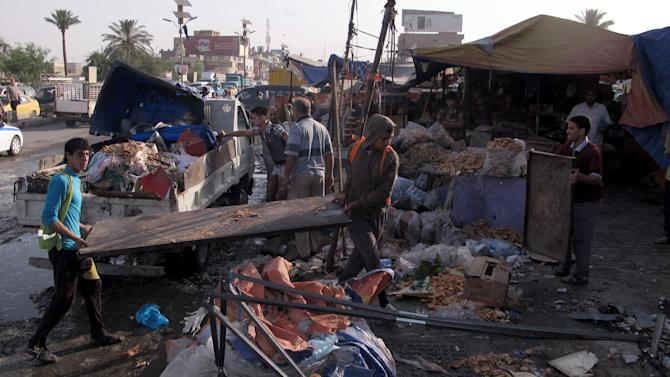 Civilians inspect the aftermath of a car bomb attack while Baghdad municipality workers clean up in Baghdad, Iraq, Thursday, May 16, 2013. A car bomb exploded near a bus station in Baghdad's main Shiite district Wednesday, the deadliest in a series of explosions that killed and wounded dozens of people, nationwide, officials said. (AP Photo/ Khalid Mohammed)