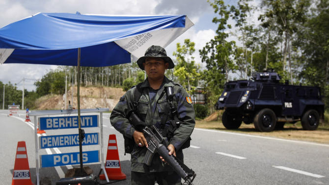 A Malaysian police officer stands guard at an outpost before the entry point to the Malaysia-Thailand border in Wang Kelian, Malaysia on Monday, May 25, 2015.  Malaysian authorities said Monday they have discovered 139 suspected graves in a series of abandoned camps used by human traffickers on the border with Thailand where Rohingya Muslims fleeing Myanmar were believed to have been held. (AP Photo/Joshua Paul)