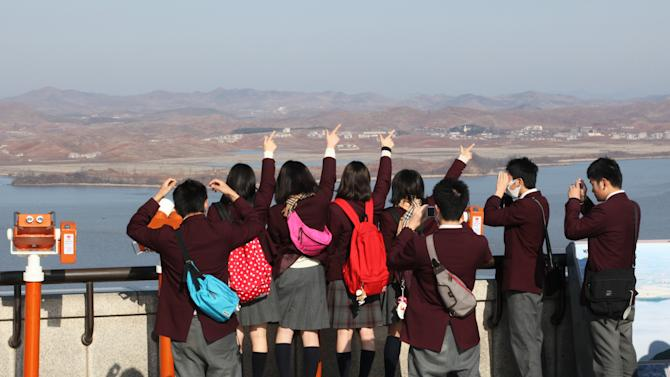 Japanese highschool students gesture toward North Korean side at the Unification Observation Post in Paju near the demilitarized zone between the two Koreas, South Korea,Thursday, March 14, 2013.   Busloads of tourists still show up to gawk at the world's most heavily fortified border, even as governments on both sides threaten to reduce each other to rubble. (AP Photo/Ahn Young-joon)