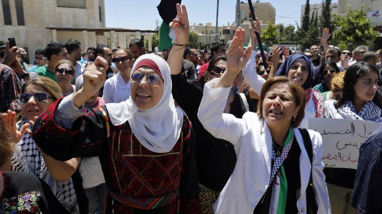 Protesters shout anti-Israel slogans during a demonstration calling for an end to the Israeli air strikes in the Gaza Strip, near the Israeli embassy in Amman