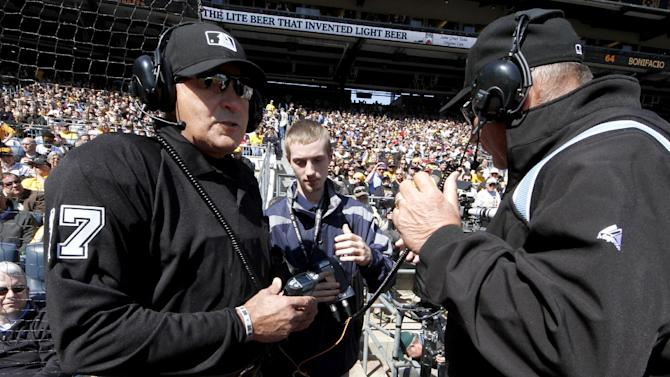 First base umpire Bob Davidson, right, and home plate umpire John Hirschbeck, left, talk over headsets as a play at first base is being reviewed in the fifth inning during the opening day baseball game between the Pittsburgh Pirates and the Chicago Cubs on Monday, March 31, 2014, in Pittsburgh. Chicago Cubs manager Rick Renteria requested a replay on an out call. (AP Photo/Gene Puskar)