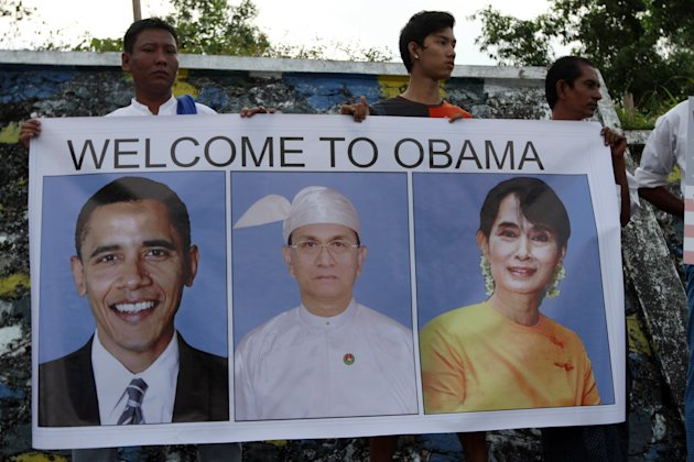People holding a poster with portraits of U.S. President Barack Obama, left, Myanmar President Thein Sein, center, and Myanmar opposition leader and Nobel laureate Aung San Suu Kyi as they wait to wel