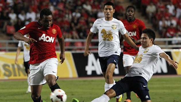 Manchester United's Anderson (L) fights for the ball with Thailand Singha All Stars' Thitipan Puangchan during their friendly soccer match at the Rajamangala national stadium in Bangkok July 13, 2013. (Reuters)