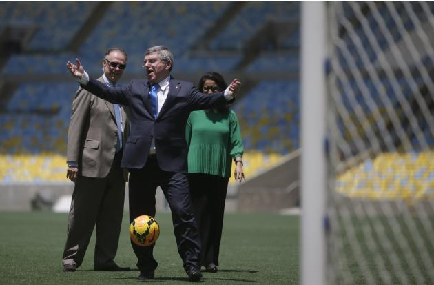 IOC President Thomas Bach gestures as he plays with a ball as President of Brazil's Olympic Committee Arthur Nuzman and IOC Evaluation Commission head Nawal El Moutawakel observe during a visit to