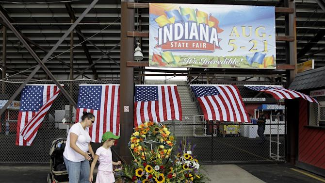 Jennifer Dominianni along with her daughter, Natania, look at a memorial in front of the Grandstand at the Indiana State Fair in Indianapolis, Monday, Aug. 15, 2011. The memorial is set-up for those who were killed when a  stage collapsed Saturday night. (AP Photo/Darron Cummings)