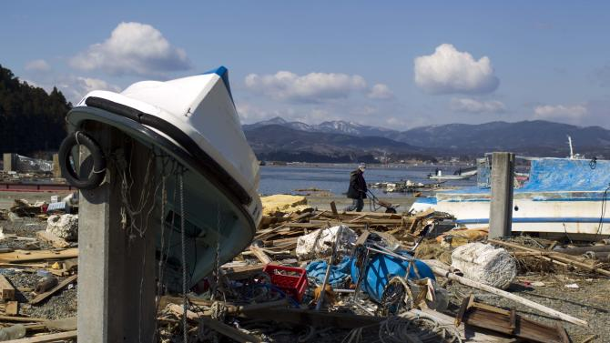 A resident of Oshima island of pushes a wheel barrow past the destroyed port as he tries to salvage belongings from his home in northeastern Japan Monday, March 28, 2011, following the March 11 earthquake and tsunami. (AP Photo/David Guttenfelder)