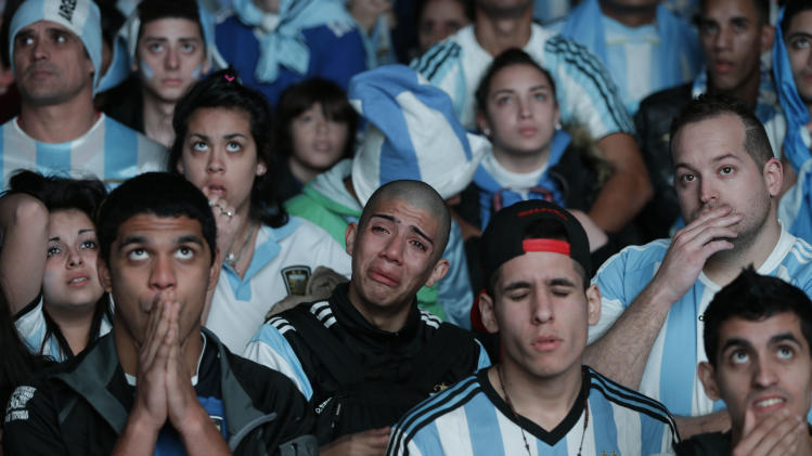 Argentina soccer fans react as their team is defeated by Germany in the World Cup final match, on an outdoor television screen set up in Buenos Aires, Argentina, Sunday, July 13, 2014. Mario Goetze volleyed in the winning goal in extra time to give Germany its fourth World Cup title with a 1-0 victory over Argentina. (AP Photo/Jorge Saenz)