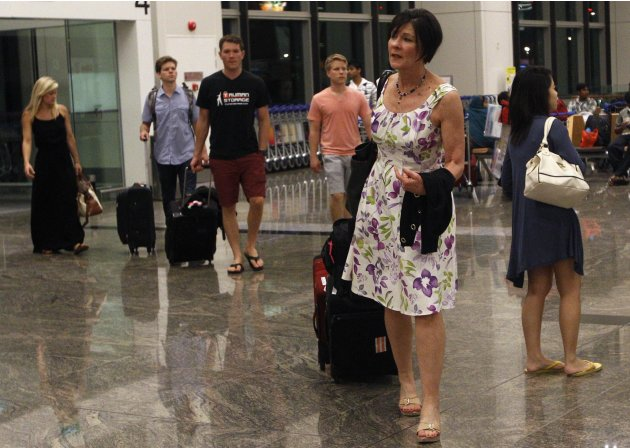 Mary Todd arrives with her family to board their Delta Airlines flight back to the U.S. at Changi Airport in Singapore