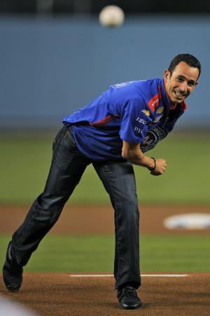 Race car driver Helio Castroneves throws out the ceremonial first pitch prior to the Los Angeles Dodgers' baseball game against the St. Louis Cardinals, Thursday, Sept. 13, 2012, in Los Angeles. (AP Photo/Mark J. Terrill)