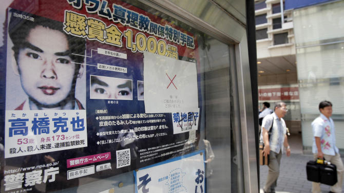 """In this Thursday, June 7, 2012 photo, a """"wanted"""" poster of former Aum Shinrikyo cult member Katsuya Takahashi is displayed outside a police station in Tokyo. Thousands of police were mobilized Friday, June 8, to hunt for the last fugitive suspected in a doomsday cult's deadly nerve gas attack on Tokyo's subway 17 years ago. (AP Photo/Koji Sasahara)"""