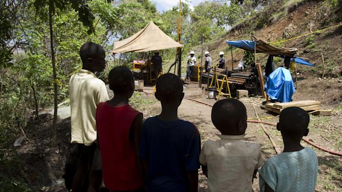 In this April 10, 2012 photo, children watch workers drill for gold, copper and silver at a temporary mountainside platform in the department of Trou Du Nord, Haiti. Haiti's land may yet hold the solution to centuries of poverty: there is gold hidden in its hills, and silver and copper too. Now, two mining companies are drilling around the clock to determine how to get those metals out, and how much it might cost.  (AP Photo/Dieu Nalio Chery)