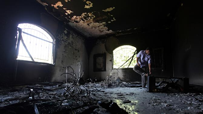 FILE - In this Thursday, Sept. 13, 2012 file photo, a Libyan man investigates the inside of the U.S. Consulate after an attack that killed four Americans, including Ambassador Chris Stevens, on the night of Tuesday, Sept. 11, 2012, in Benghazi, Libya. A man linked to the attack on the U.S. consulate in Benghazi has been conditionally released by Tunisian authorities due to lack of evidence, his lawyer said Tuesday Jan. 8, 2013. The release of Ali Harzi, a 26-year-old Tunisian, appears to represent a blow to the investigation of the Sept. 11 attack on the consulate in Libya. (AP Photo/Mohammad Hannon, File)