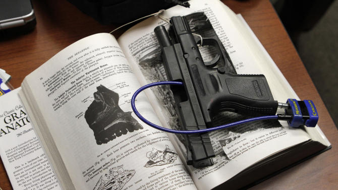 A Springfield Armory semi-automatic pistol, that police say was used by Philip Markoff as a murder weapon in the shooting death of Julissa Brisman, whom he met through Craigslist, rests in a hand-cut cavity in a text book on a table at a news conference held by Massachusetts Suffolk District Attorney Daniel Conley and other law enforcement officials in Boston on Thursday, March 31, 2011. (AP Photo/Steven Senne)