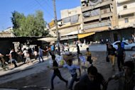 Syrians run for cover as a helicopter hovers over the northern city of Aleppo. Rebels accused strongman Bashar al-Assad on Tuesday of moving chemical weapons to Syria&#39;s borders, a day after his beleaguered regime said it would use its stockpiles if attacked