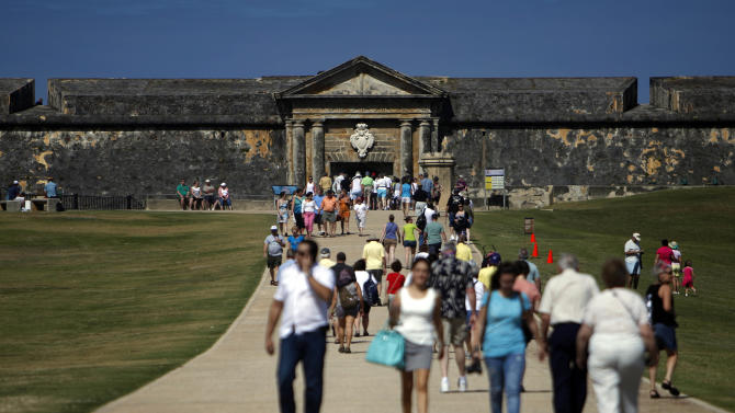 """Tourists walk near the 16th century Spanish fort called El Morro in Old San Juan, Puerto Rico, Jan. 24, 2013. There's an entrance fee to enter the Castillo San Felipe del Morro, but the best way to enjoy this U.S. National Historic Site requires no money at all. The fort that towers over San Juan Bay, known universally as just """"El Morro,"""" is a great place to stroll, especially at sunset. The massive rolling expanse of grass at the foot of the fort has spectacular views in any direction. It's a popular place to picnic and fly a kite, sold by nearby street vendors. (AP Photo/Ricardo Arduengo)"""