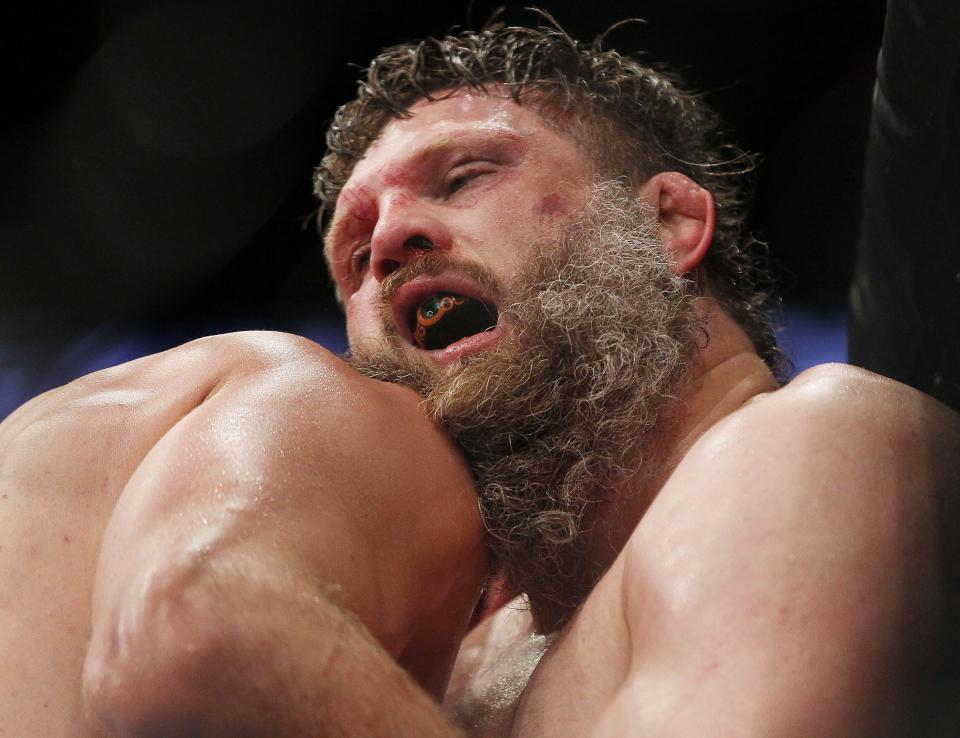 A hurting Roy Nelson hangs on in the third round of his heavyweight bout against Stipe Miocic during UFC 161 in Winnipeg, Manitoba on Saturday June 15, 2013.  (AP Photo/The Canadian Press, John Woods)