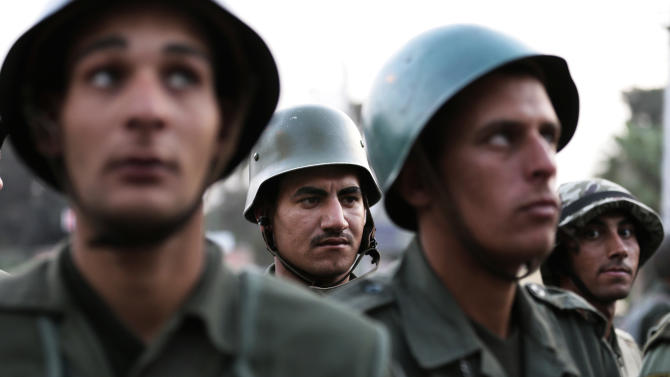 Egyptian army soldiers stand guard in front of the presidential palace in Cairo, Egypt, Sunday, Dec. 9, 2012. Egypt's liberal opposition called for more protests Sunday, seeking to keep up the momentum of its street campaign after the president made a partial concession overnight but refused its main demand he rescind a draft constitution going to a referendum on Dec. 15. (AP Photo/Hassan Ammar)