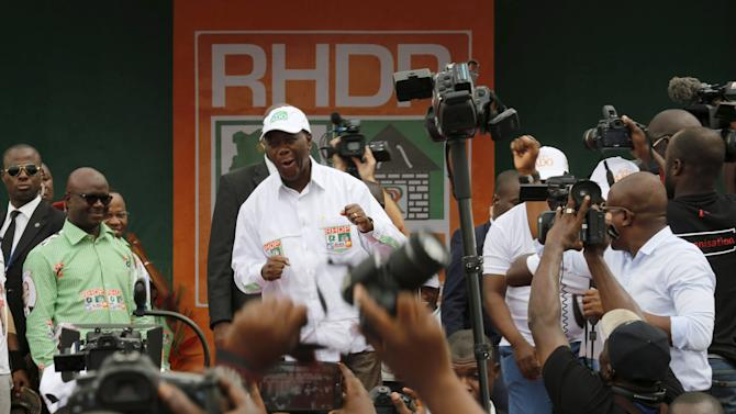 Ivory Coast's President Alassane Ouattara of the Rally of the Houphouetists for Democracy and Peace (RHDP) party dances during a campaign rally at Jean Paul II space in Yamoussoukro