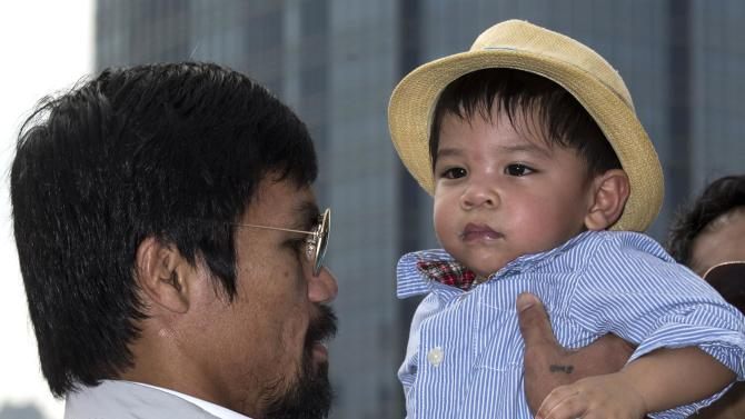 Boxer Manny Pacquiao of the Philippines holds up a child as he attends a promotional event in Hong Kong
