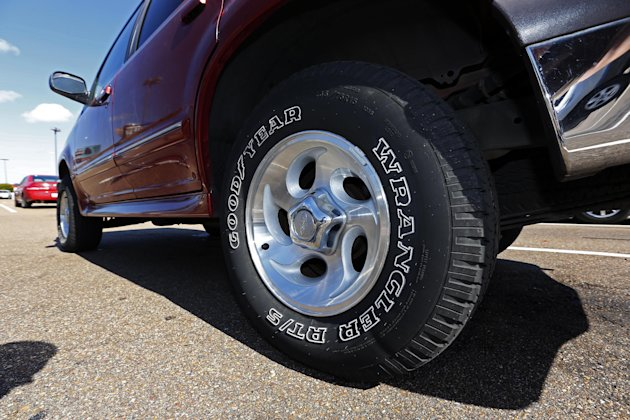 This Tuesday, Oct. 23, 2012, photo, shows a Ford Explorer with Goodyear tires in Jackson, Miss. Goodyear Tire & Rubber Co. said Friday, Oct. 26, 2012 that its third-quarter net income fell by nearly one-third as lower tire sales in Europe offset cost savings and higher North American profits. The company's results fell short of Wall Street expectations, and it said in a statement that more cost cuts are coming because of economic uncertainty. (AP Photo/Rogelio V. Solis)