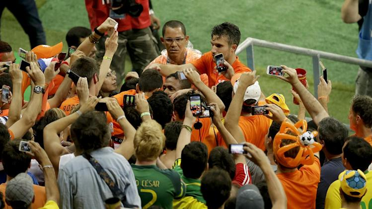 Netherlands' Robin van Persie celebrates with fans after winning the World Cup quarterfinal soccer match between the Netherlands and Costa Rica at the Arena Fonte Nova in Salvador, Brazil, Saturday, July 5, 2014. Netherlands beat Costa Rica 4-3 on penalties to reach semifinals of the World Cup