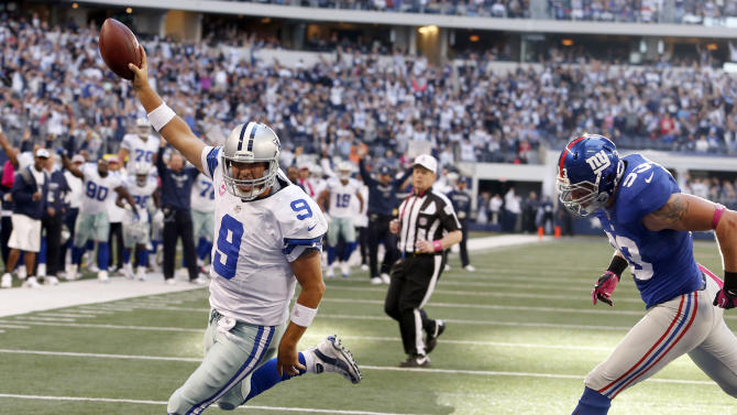 Dallas Cowboys quarterback Tony Romo (9) gets past New York Giants middle linebacker Chase Blackburn (93) to score a touchdwon during the second half of an NFL football game, Sunday, Oct. 28, 2012, in Arlington, Texas. (AP Photo/Sharon Ellman)
