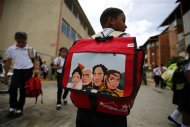 A student carrying a backpack bearing the image of national independence hero Simon Bolivar (2nd R), walks as they leave the school in Ciudad Caribia outside Caracas September 19, 2013. REUTERS/Jorge Silva
