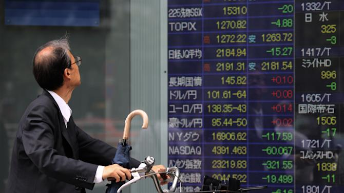 A man looks at an electronic stock board of a securities firm in Tokyo, Wednesday, July 9, 2014. Asian stock markets fell for a third day Wednesday as caution spread ahead of corporate earnings and after record highs on Wall Street. (AP Photo/Eugene Hoshiko)