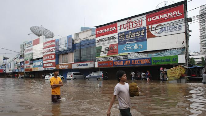 People wade through a flooded street in Jakarta, Indonesia, Thursday, Jan. 17, 2013. Floods regularly hit parts of Jakarta in the rainy season, but Thursday's inundation following an intense rain storm appeared especially widespread. (AP Photo/Tatan Syuflana)