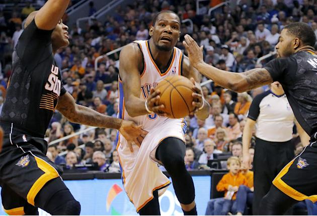 Oklahoma City Thunder forward Kevin Durant, center, drives against Phoenix Suns' P.J. Tucker, left, and Marcus Morris during the first half of an NBA basketball game, Thursday, March 6, 2014, in P