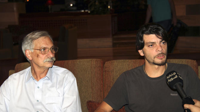 Two Italian electrical engineers, Oriano Cantani, 64, left, and Domenico Tedeschi, 36, who were captured eight days ago by unknown militants, speak to reporters after their release by the Syrian army in Damascus, Syria, Friday July  27, 2012. The two engineers who worked at the Deir Ali power plant some 18 miles (30 Kilometers) south of `Damascus, two drivers and a Russian expert were stopped by five or six masked men when they were on their way to the airport on 18 July 2012. (AP Photo/Bassem Tellawi)