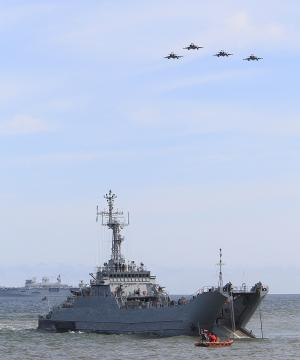 War planes fly over a ship as NATO troops participate…